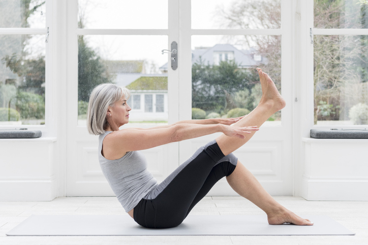 senior woman does yoga at home