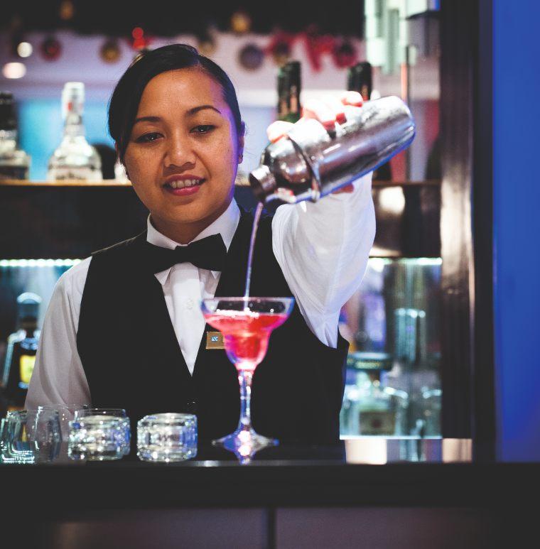 Waitress serving a cocktail on Fred Olsen's Boudicca